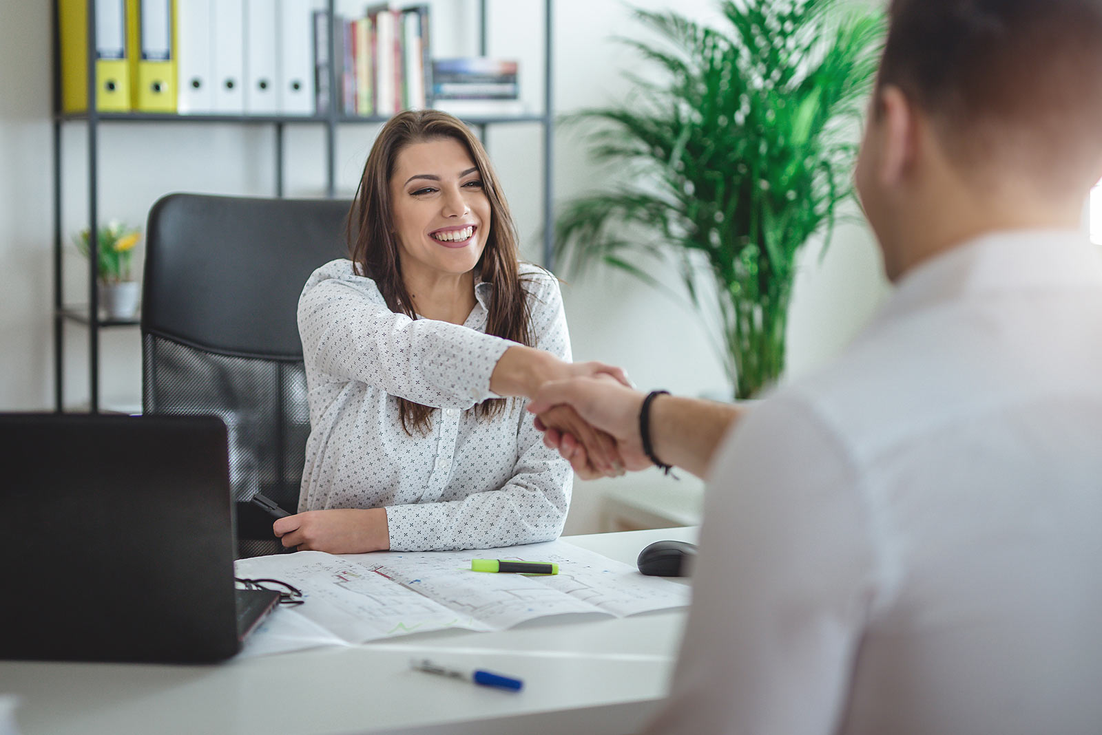 Human resources manager shaking hands with new employee